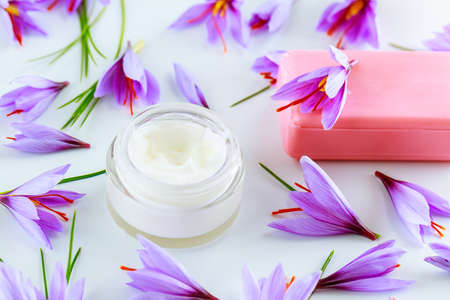 Saffron flowers on a white background and cosmetic cream with saffron soap. Banque d'images