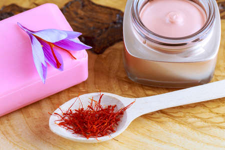 Saffron flower on soap and cosmetic cream on a wooden background. Cream with saffron extracts. Dry saffron in wooden spoon.