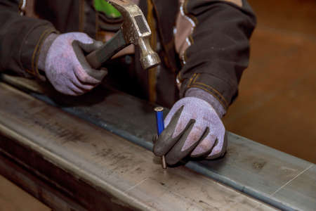 marking on a metal surface for drilling holes with a square and a caliper. Hammer, nail punch. Stock Photo
