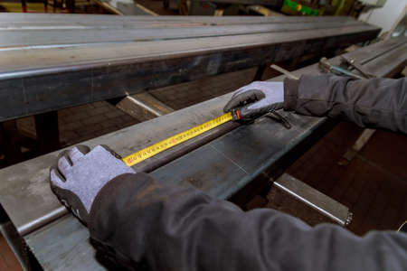 worker measures markings on a metal surface for drilling holes.