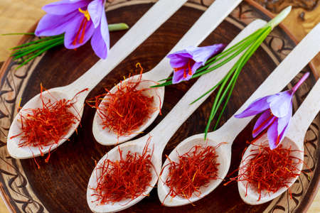 saffron in wooden spoon. dried saffron spice in a wooden spoon on ceramic plate. Saffron spice used in food and traditional herbal medicine