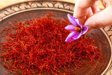 Dried saffron with a flower in a patterned ceramic plate. Saffron spice used in food and traditional herbal medicine