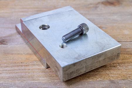 Hex head bolt. screw thread in a steel billet on a wooden board.