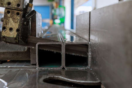 Cutting steel profiles and pipes on a band saw in production.