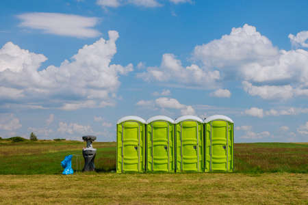 Portable toilet on the grass on a background of clouds. Mobile toilet. Standard-Bild