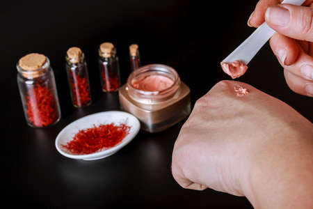 Saffron stamens are packaged in small glass jars. A girl smears her hands with a cosmetic cream with saffron extract. Stock Photo