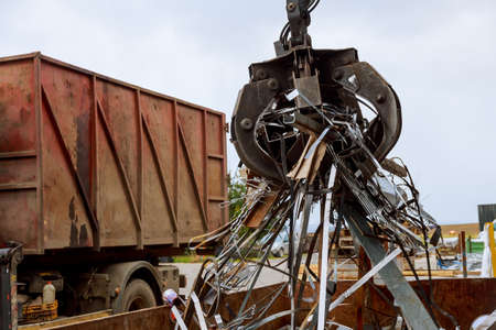 Loading scrap metal into a truck. Crane grabber loading metal rusty scrap in the dock