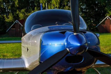 Blue light small plane on a grass field.