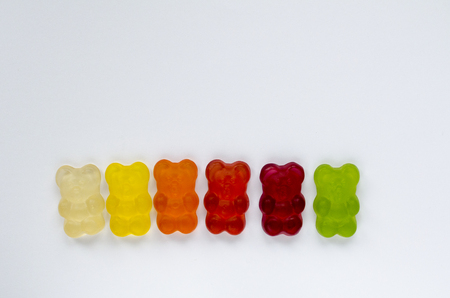 line of colored marmalade bears isolated on white background