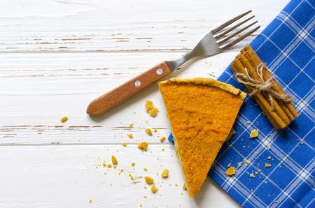 Pumpkin  pie, cinnamon sticks, autumn dry leaves on white wooden tabl Stock Photo