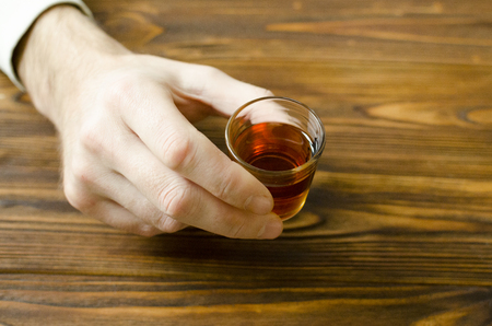 hand hold small glass with alcohol drink on wooden table
