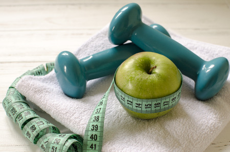 Dumbbells, green apple, towel, centimeter on white wooden background with space  for text Stock Photo