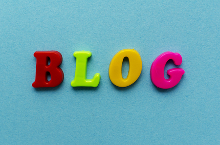 word blog from plastic magnetic colored letters on blue paper background