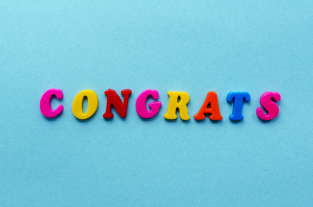 word congrats from magnetic letters on blue paper background