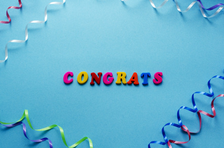 word congrats from magnetic letters and serpentine on blue paper background