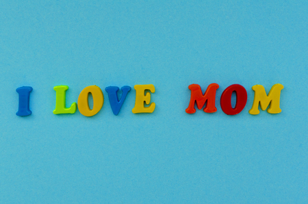 colorful text  i love mom  of magnetic letters on blue paper background