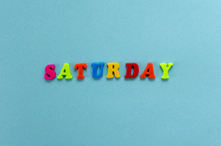 word saturday of colored plastic magnetic letters on blue paper background Stock Photo