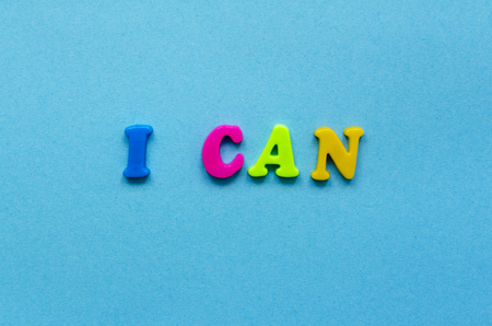 phrase i can of colored plastic magnetic letters on blue paper background
