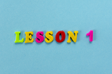 word lesson of colored plastic magnetic letters on blue paper background
