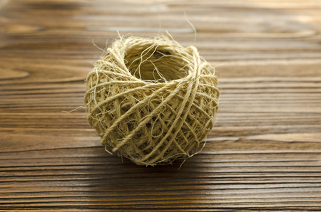 tangle of twine on brown wooden background
