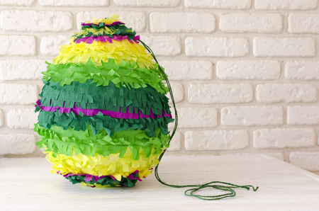 colored paper pinata on white wooden table Stock Photo