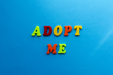 text adopt me from plastic colored letters on blue paper background