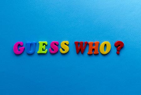 tekst raad eens wie? van plastic gekleurde letters op een blauwe papieren achtergrond