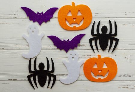 felt pumpkin, spider, ghost, bat on wooden background