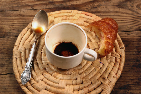 the residue: Empty cup of coffee with spoon and unfinished croissant on wicker background Stock Photo