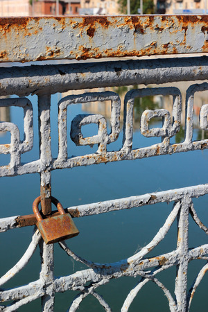 conquers: A lone padlock on old rusty bridge. Love conquers all.