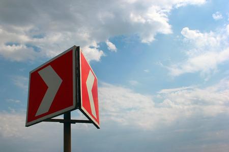 multidirectional: Red white warning arrow on blue sky background