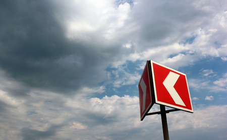 multidirectional: Red and white warning arrow on cloudy sky background