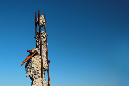 Rusty ends of steel reinforcing bars sticking out of demolished concrete pole on blue sky background