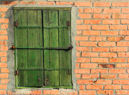 bolted: Old bolted wooden window shutters on red brick wall Stock Photo