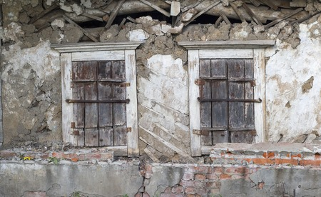 dilapidated wall: Old dilapidated wall with two shuttered windows.