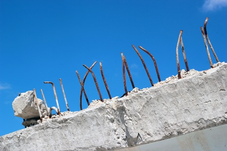 Rusty ends of steel reinforcing bars sticking out of demolished concrete block on blue sky background