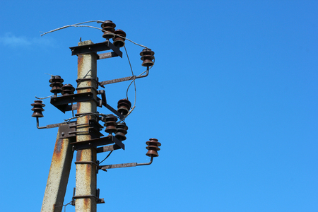 outage: Old rusty electrical pole with insulators and broken wires against blue sky background