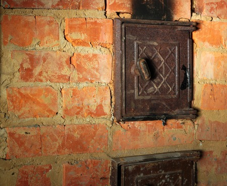 sooty: Rusty closed metal door in red brick sooty furnace. Stock Photo