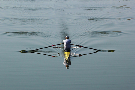 sculling: One rower in a boat, rowing on the tranquil river. Stock Photo