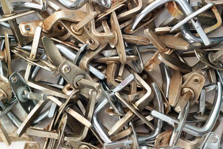 metalware: Pile of old dirty metal door handles. Stock Photo