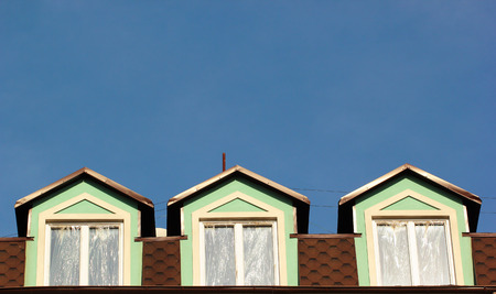 attic: Three attic windows on roof against the blue sky background