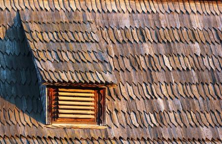 attic window: Small gridded attic window in old seasoned wooden shingle tiled roof