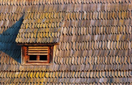 attic window: Small attic window in old seasoned wooden shingle tiled roof