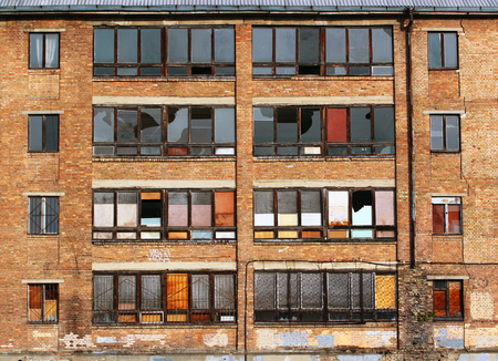 Old brick school building with gridded and broken windows Stock Photo
