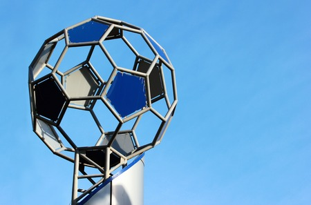 sphere base: symbolic metal soccer ball on socle against blue sky background Stock Photo