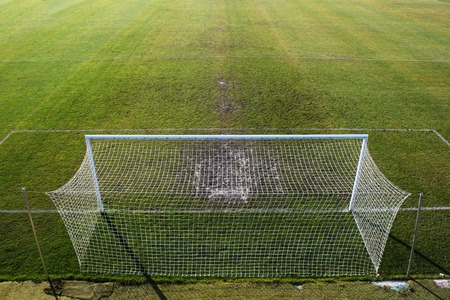 trampled: Empty soccer field and trampled grass near the gate. View from above