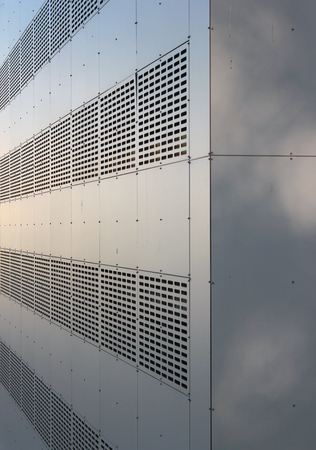 buiding: Perforated gray metal wall of industrial buiding