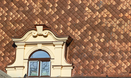 Shiny dirty copper roofing with attic window