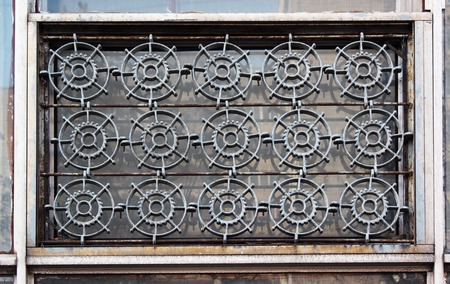 grate: Old windows with iron grate shaped like a cogwheels