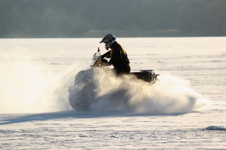 Quad bike's driver rides over frozen lake.